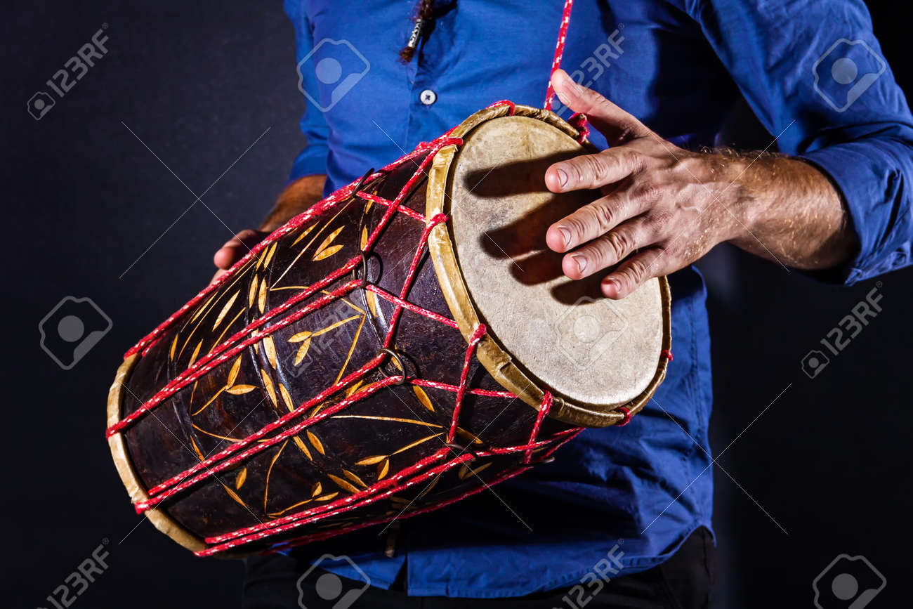 Closeup drummer male hands with jembe. Man is drumming on wooden ethnic drum. Percussion musical instrument. Musician is playing live ethno rhytm music. Summer festival concept. Modern art hobby. - 173235878