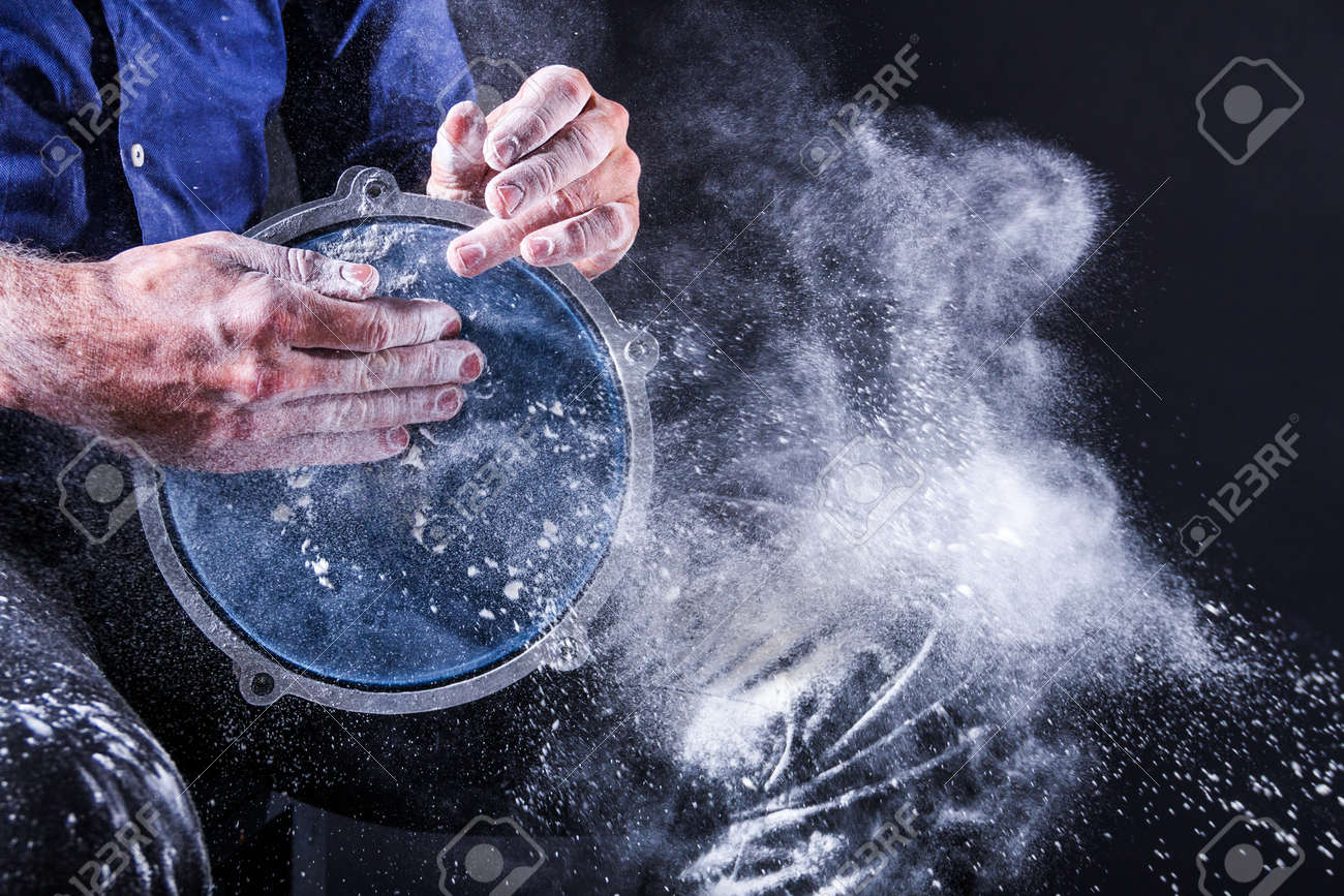 Man is playing on djembe drum, covered with talcum powder. Flour splashes on dark background. Summer festival concert performance. Ethnic rhythm. Percussion musical instruments and culture concept. - 173294071