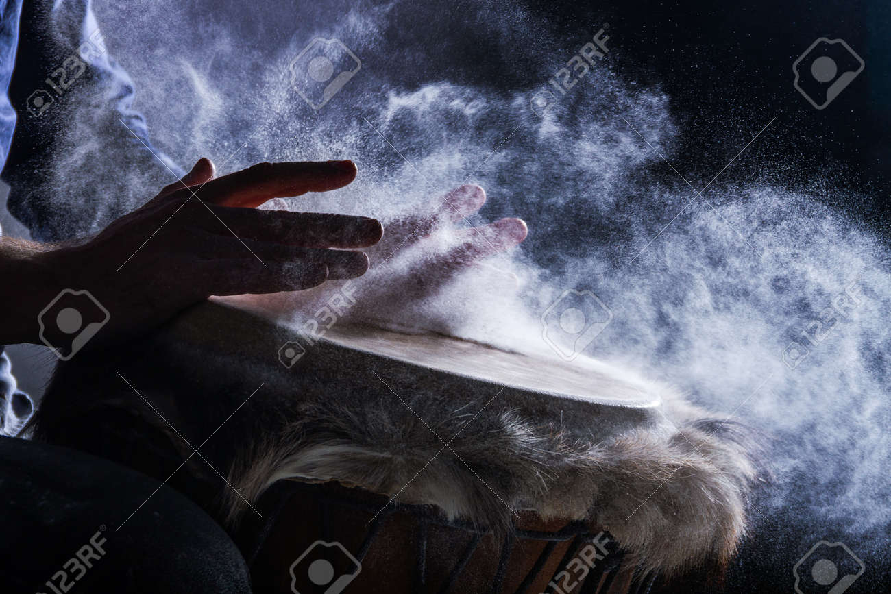 Man is playing on djembe drum, covered with talcum powder. Flour splashes on dark background. Summer festival concert performance. Ethnic rhythm. Percussion musical instruments and culture concept. - 173294075