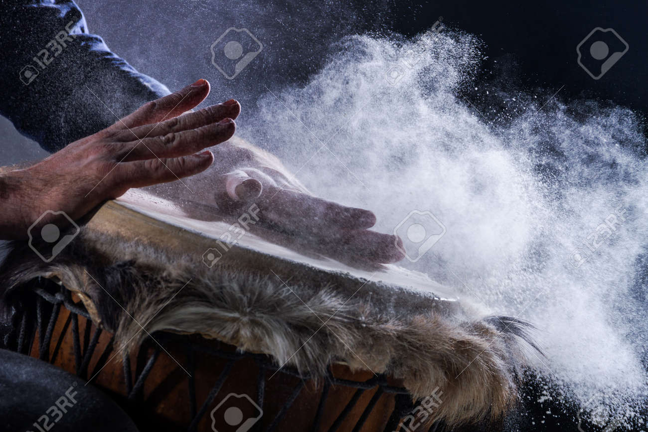 Man is playing on djembe drum, covered with talcum powder. Flour splashes on dark background. Summer festival concert performance. Ethnic rhythm. Percussion musical instruments and culture concept. - 173294077