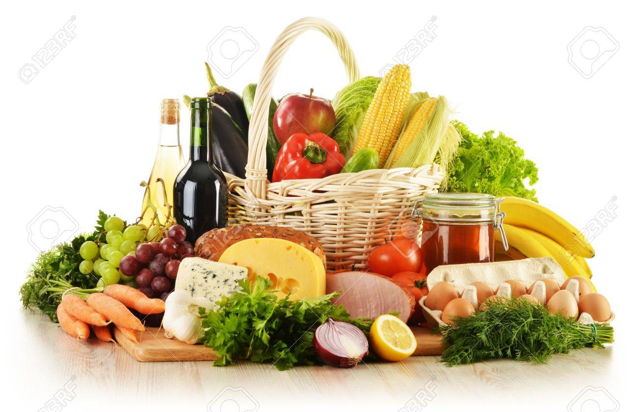 Composition with groceries in wicker basket on kitchen table Stock Photo - 15375757