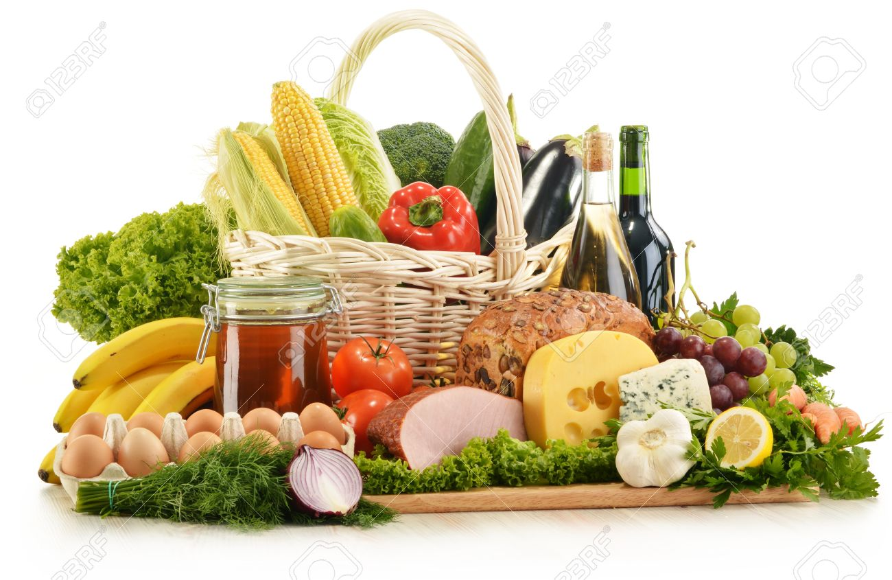 Composition With Groceries In Wicker Basket On Kitchen Table Stock