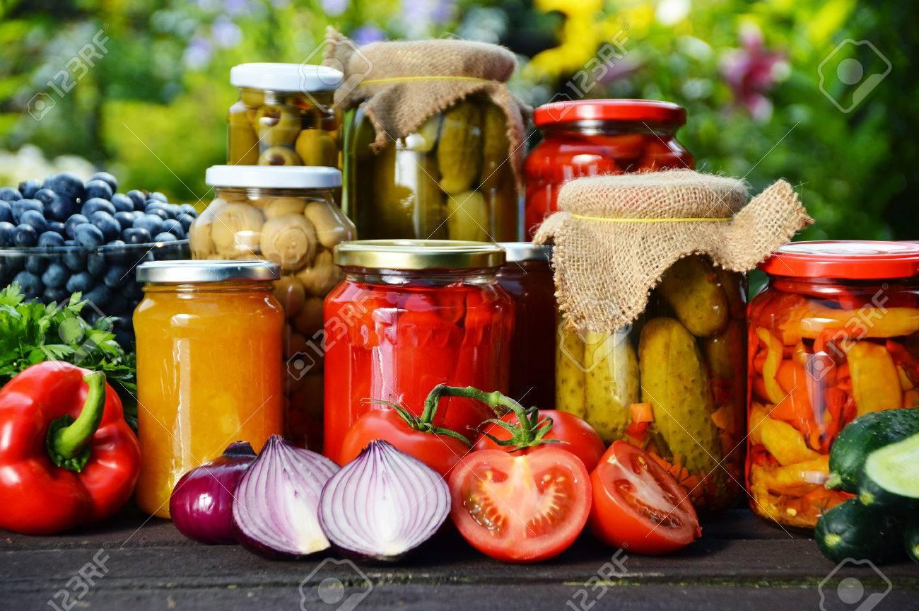 Jars of pickled vegetables in the garden. - 32314868