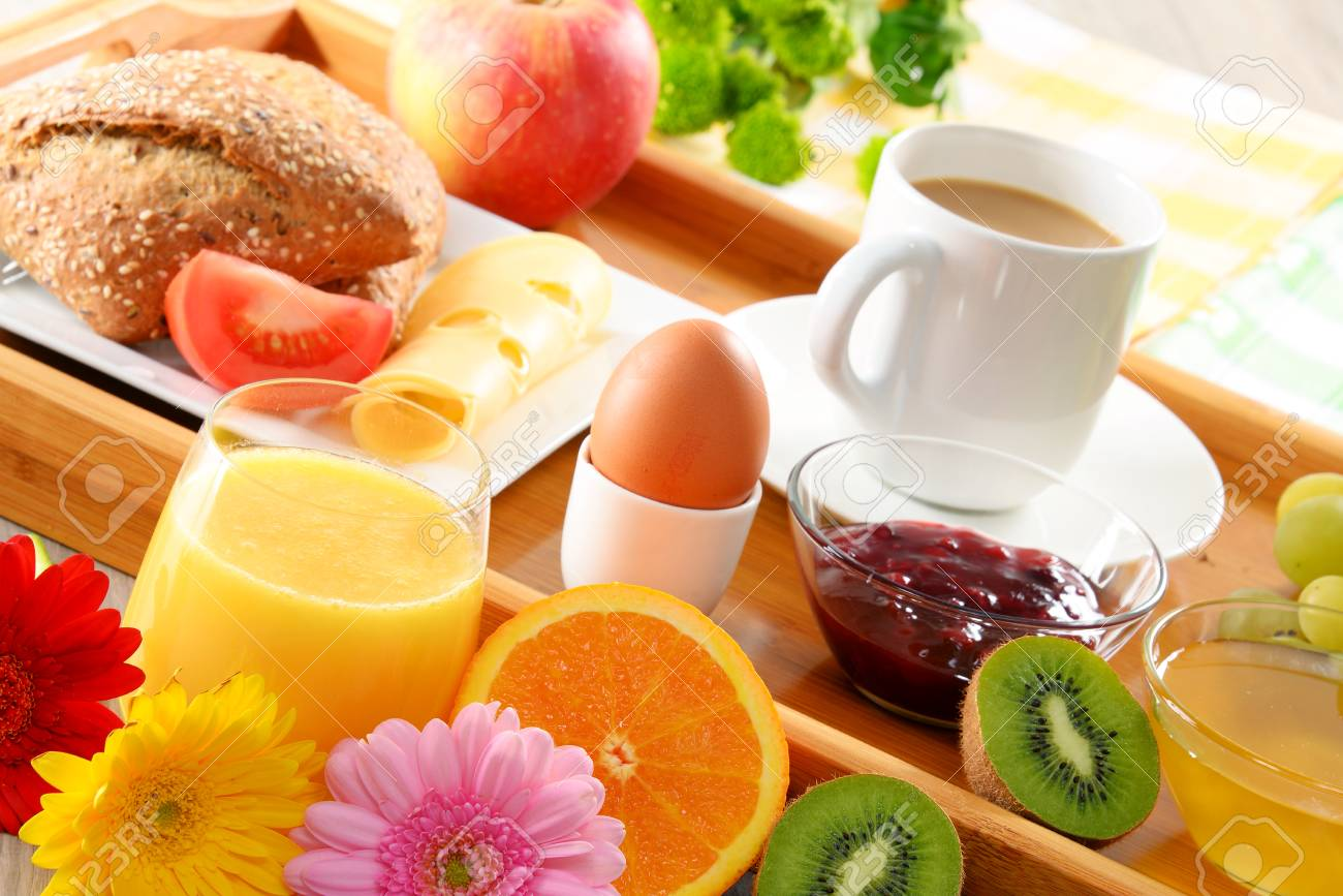 Breakfast on tray served with coffee, orange juice, egg, rolls and honey. Balanced diet. - 46514464