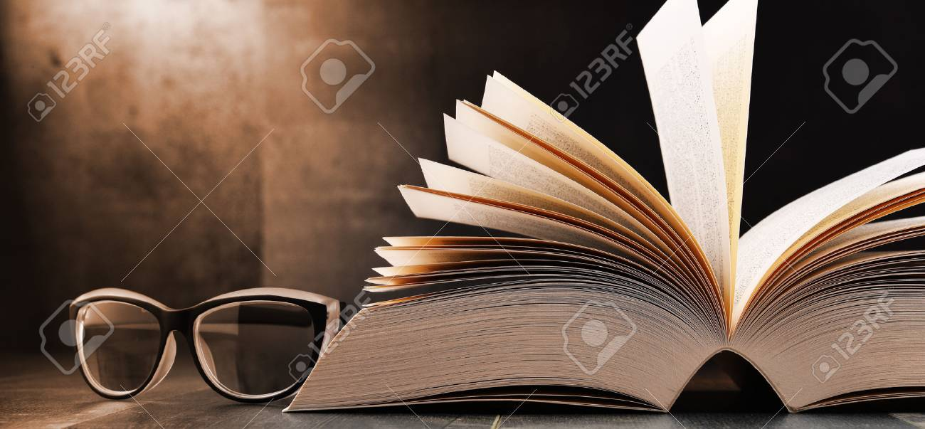 Composition with open book and glasses on the table. - 87835384