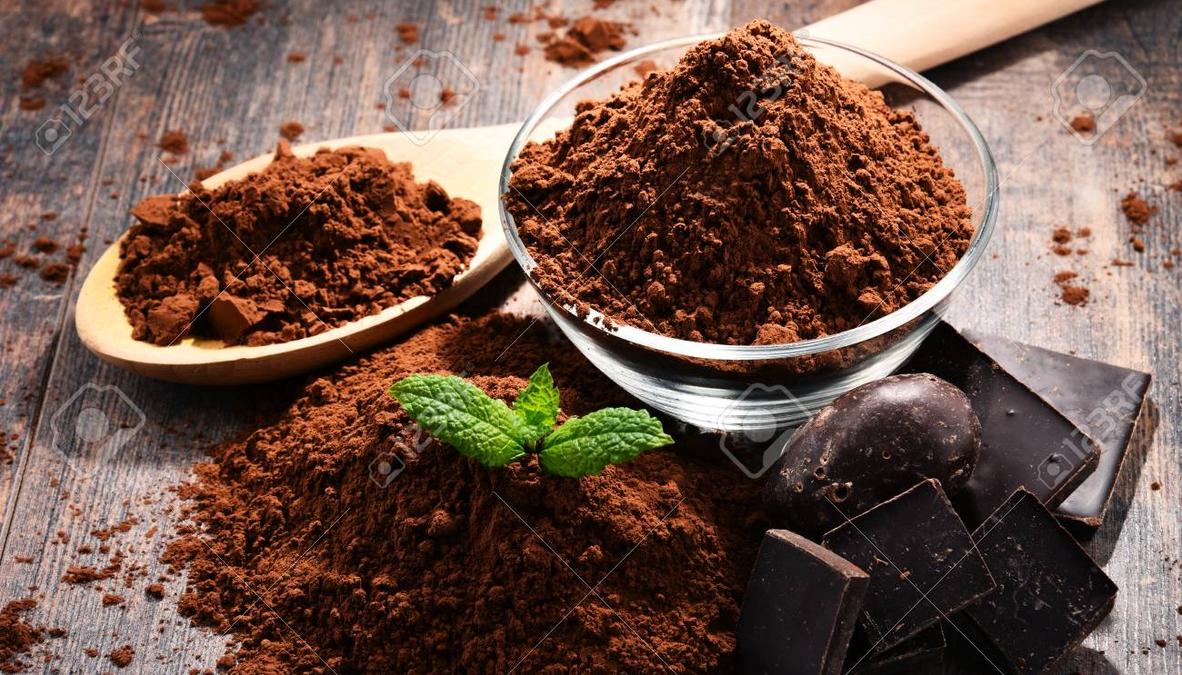Composition with bowl of cocoa powder on wooden table. - 91355121