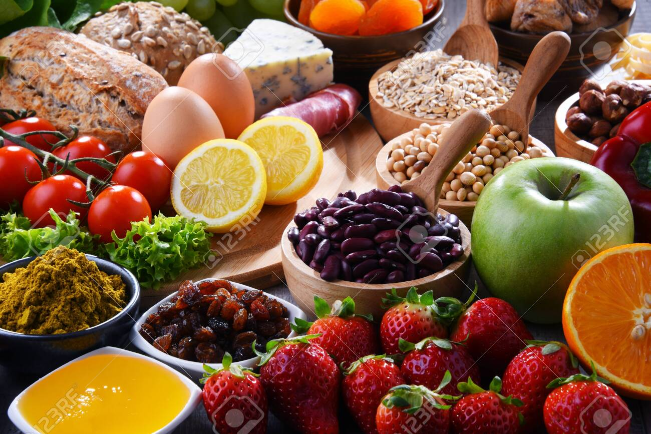 Composition with assorted organic food products on wooden kitchen table. - 121461006