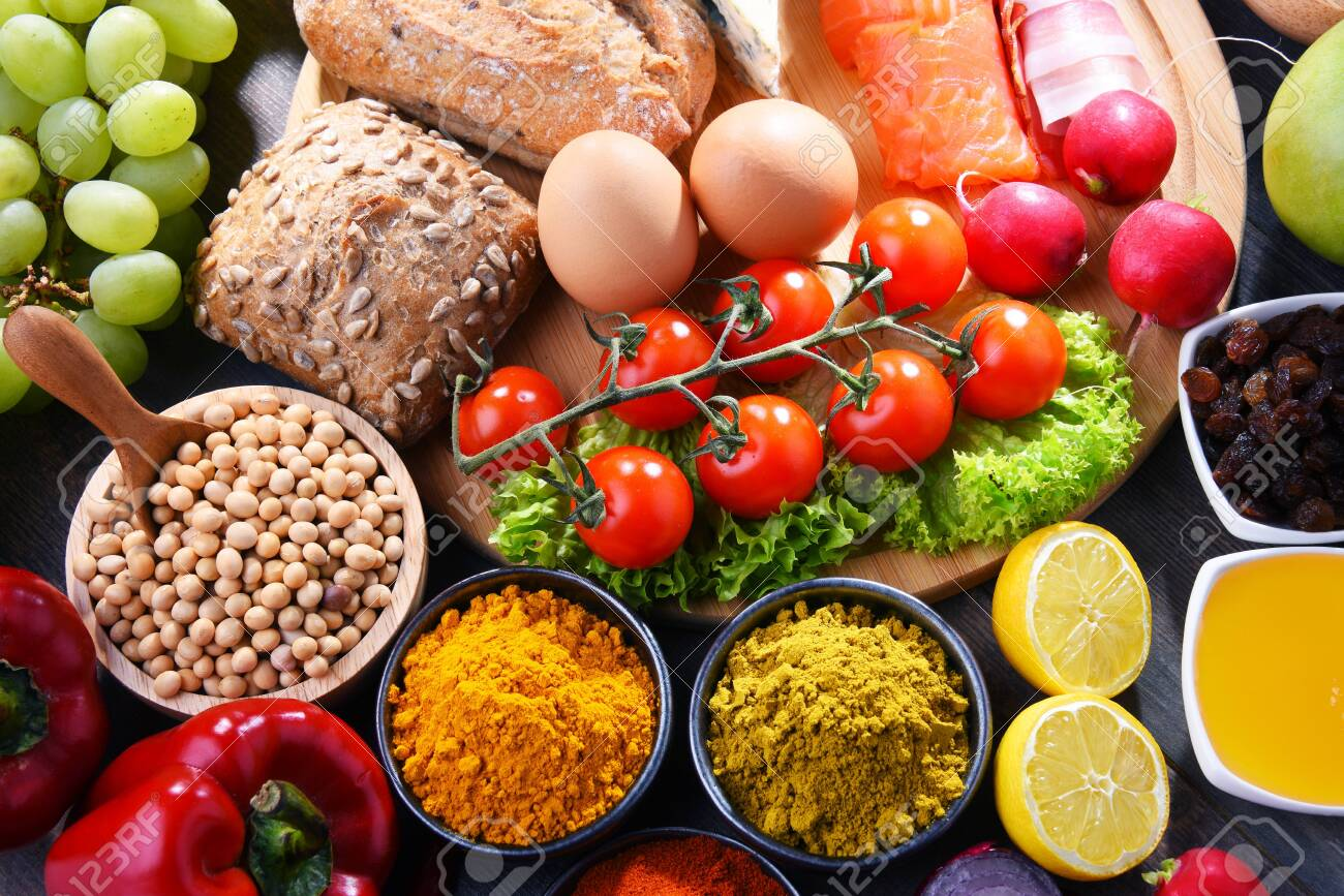 Composition with assorted organic food products on wooden kitchen table. - 123722580