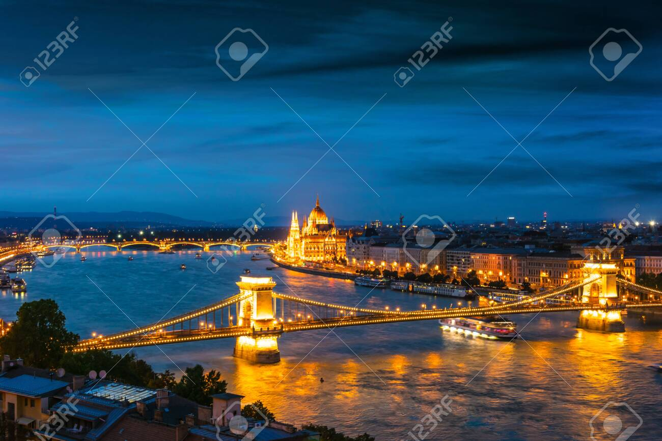 Panoramic view of Budapest with Hungarian Parliament Building on the bank of the Danube and Chain Bridge by night - 128964467