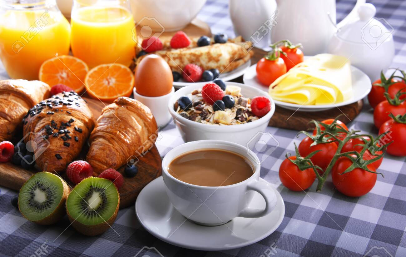 Breakfast served with coffee, orange juice, croissants, pancake, egg, cereals and fruits. - 135302334
