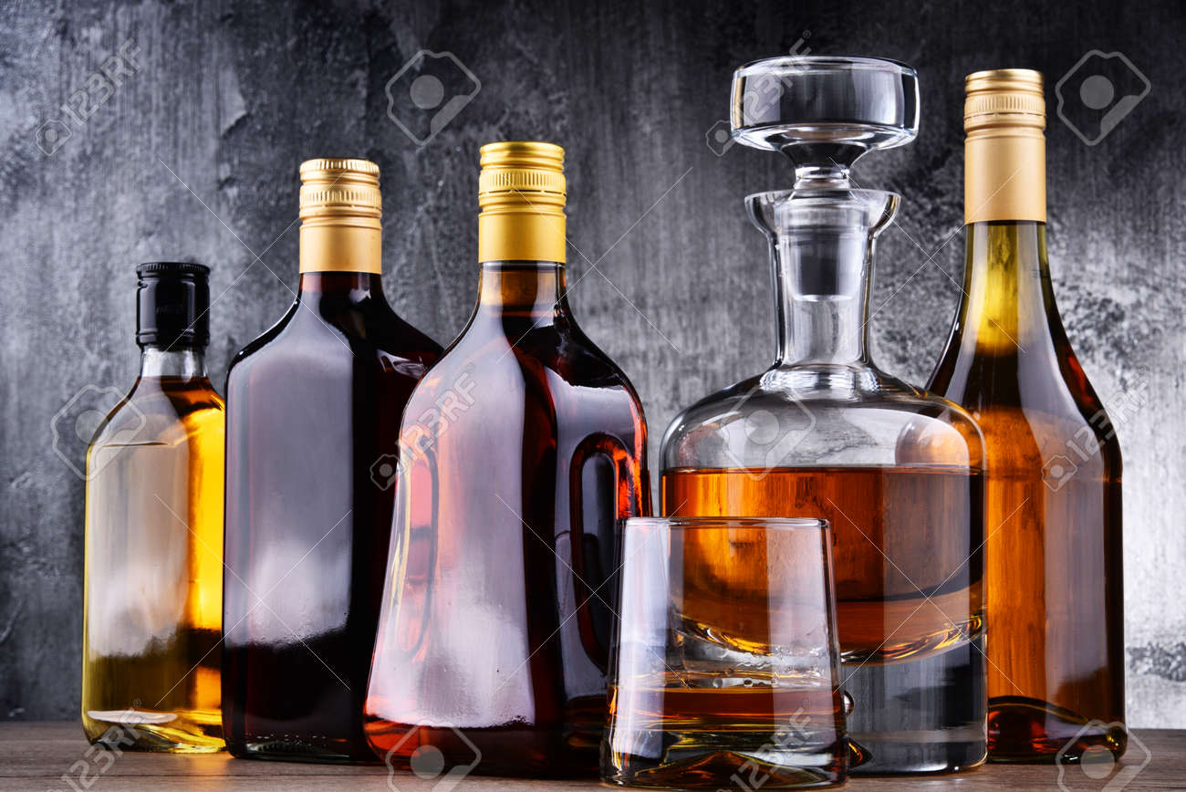 Composition with carafe and bottles of assorted alcoholic beverages. - 152187545