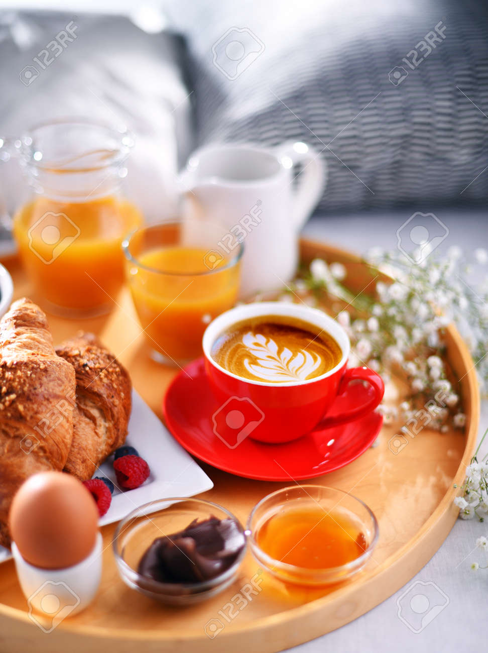 A tray with breakfast on a bed in a hotel room. - 169105200