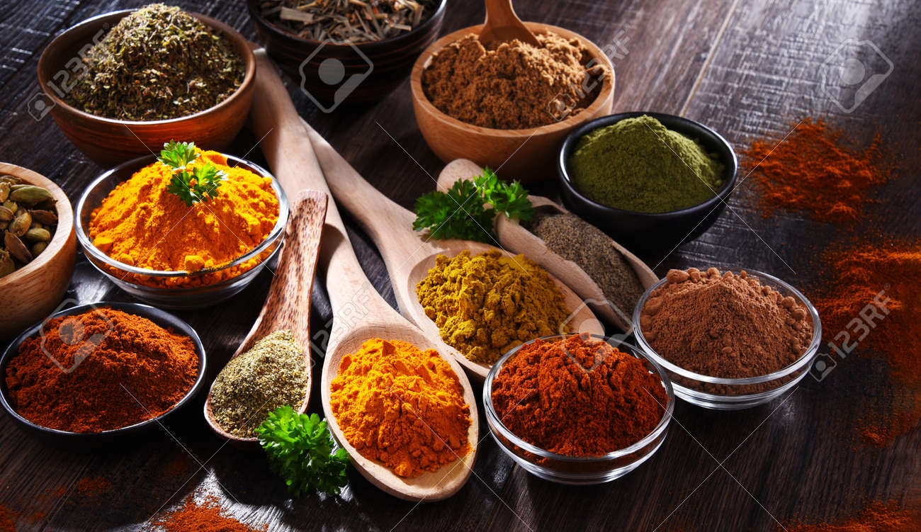 Variety of spices on wooden kitchen table. - 169105205