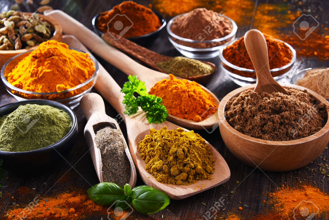 Variety of spices on wooden kitchen table. - 168771559