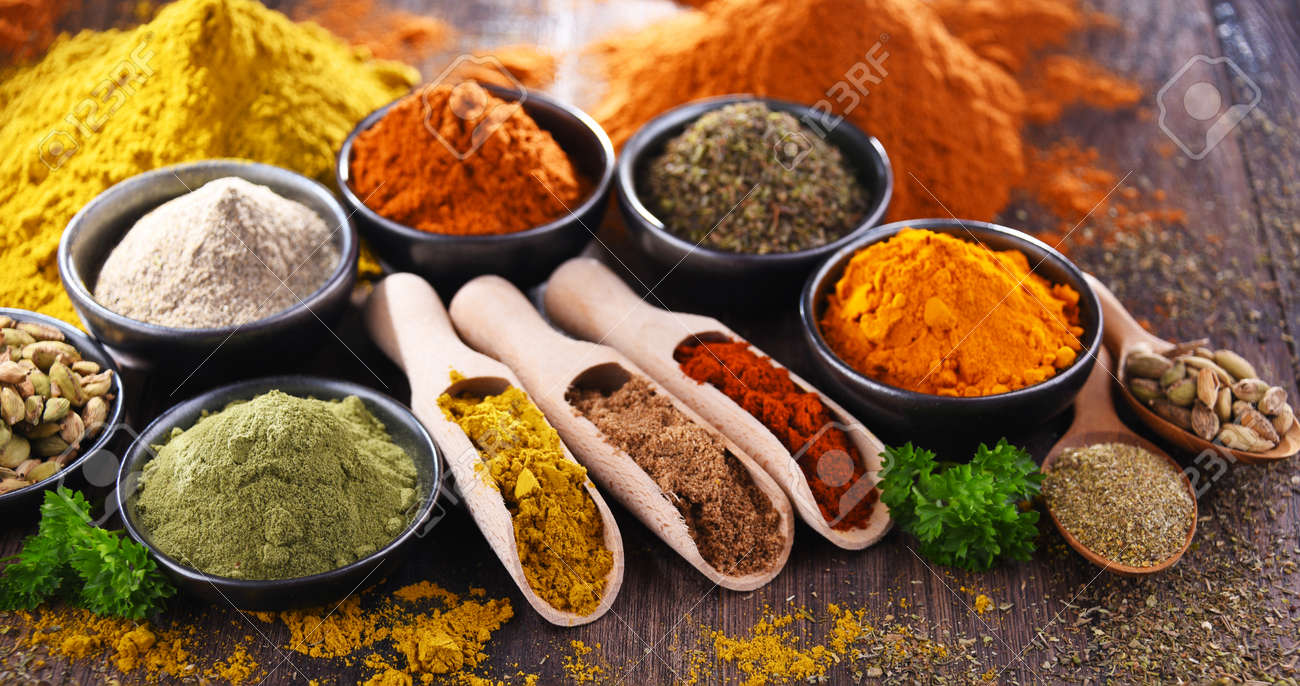 Variety of spices on wooden kitchen table. - 168771563
