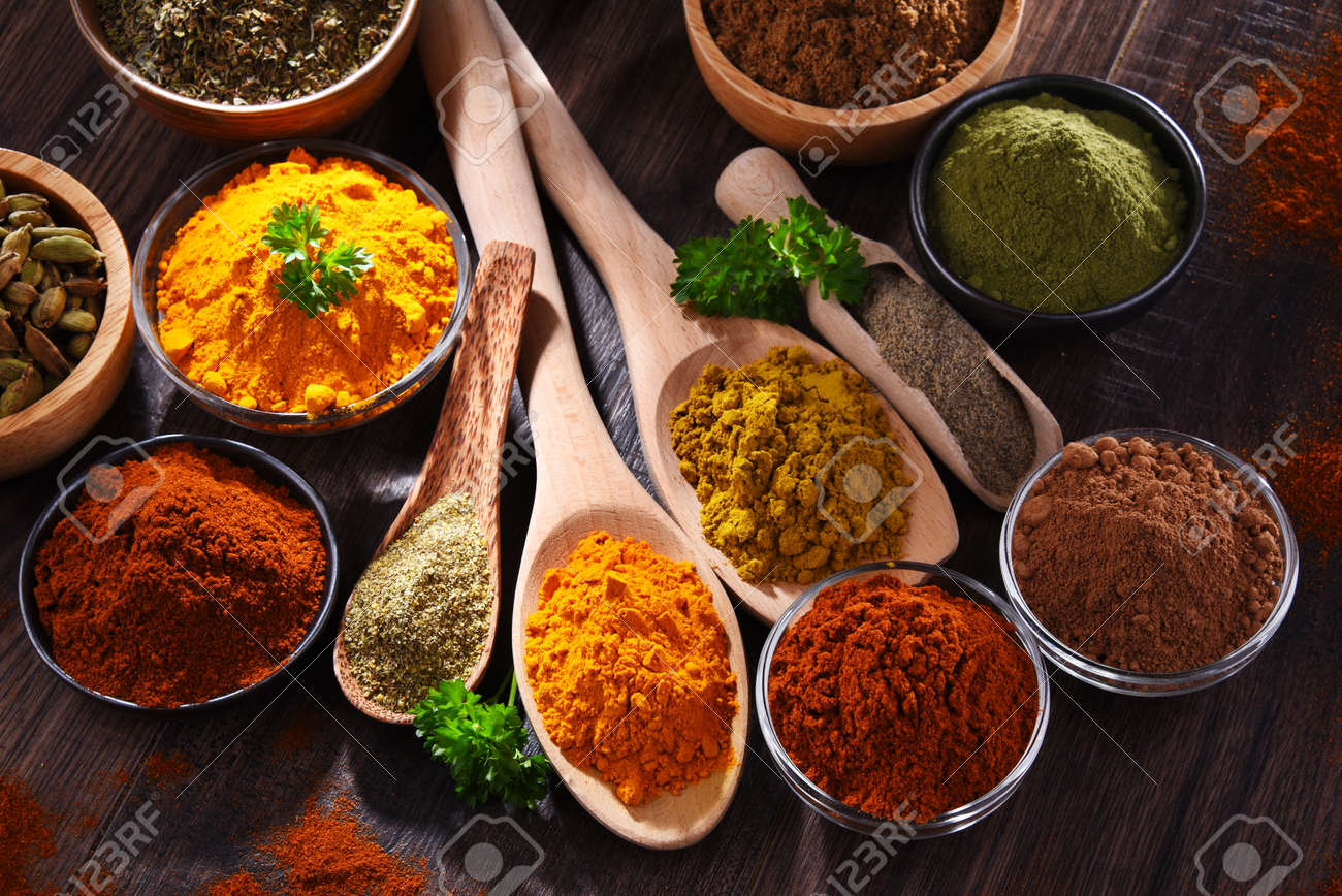 Variety of spices on wooden kitchen table. - 169105265