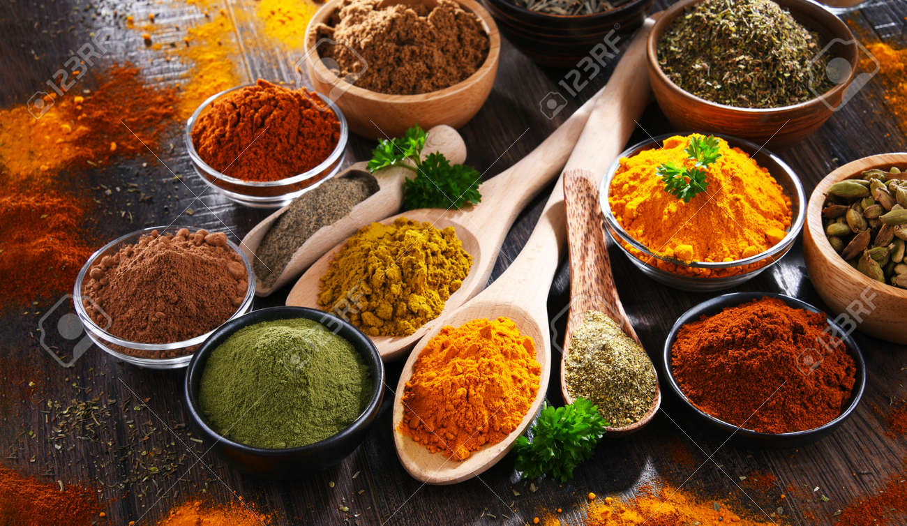 Variety of spices on wooden kitchen table. - 168771566