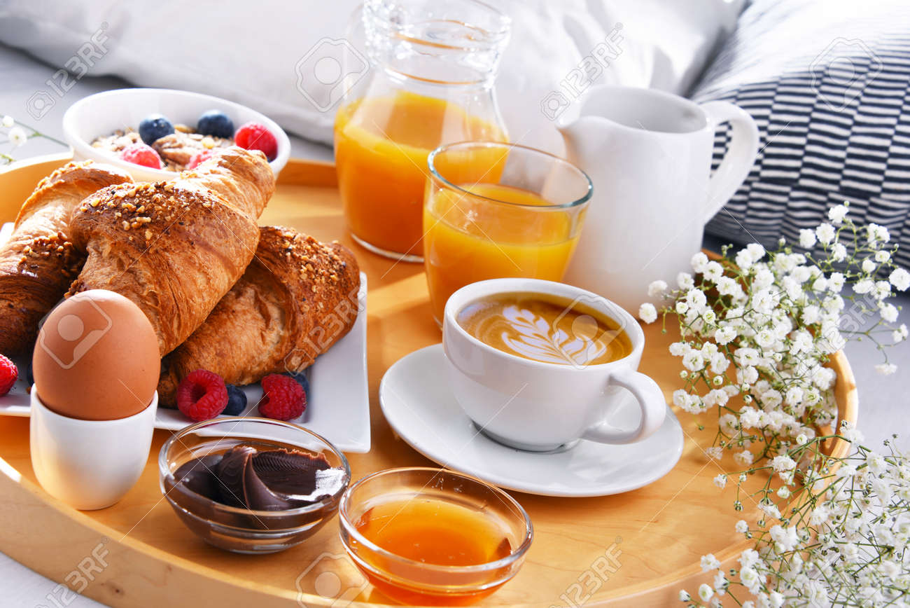 A tray with breakfast on a bed in a hotel room. - 168771565