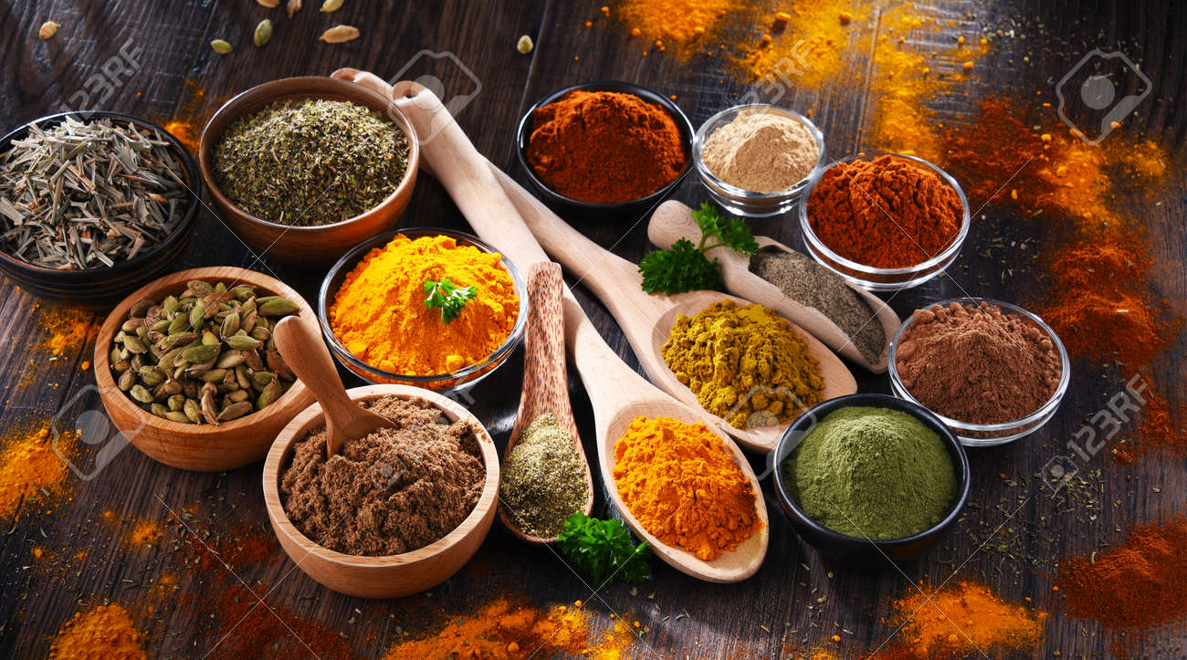 Variety of spices on wooden kitchen table. - 168771569