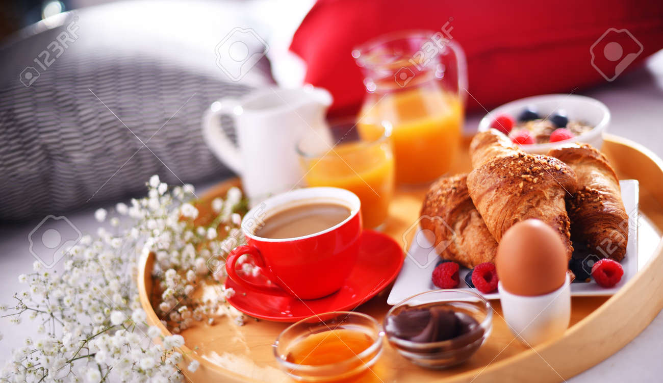 A tray with breakfast on a bed in a hotel room. - 168771570