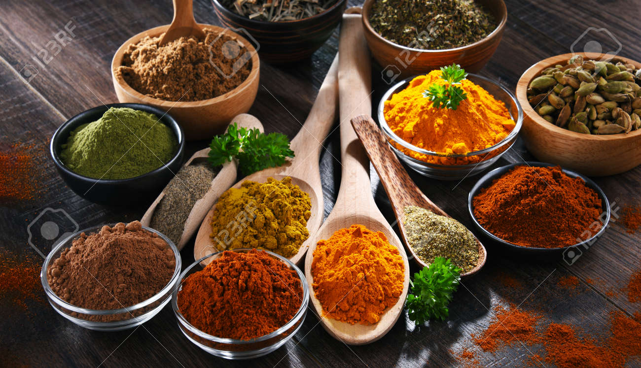 Variety of spices on wooden kitchen table. - 168771571