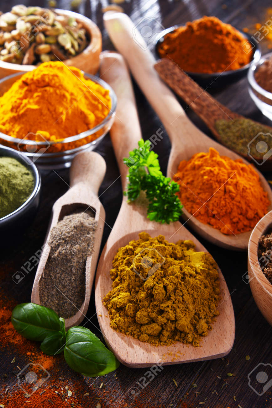 Variety of spices on wooden kitchen table. - 169105268