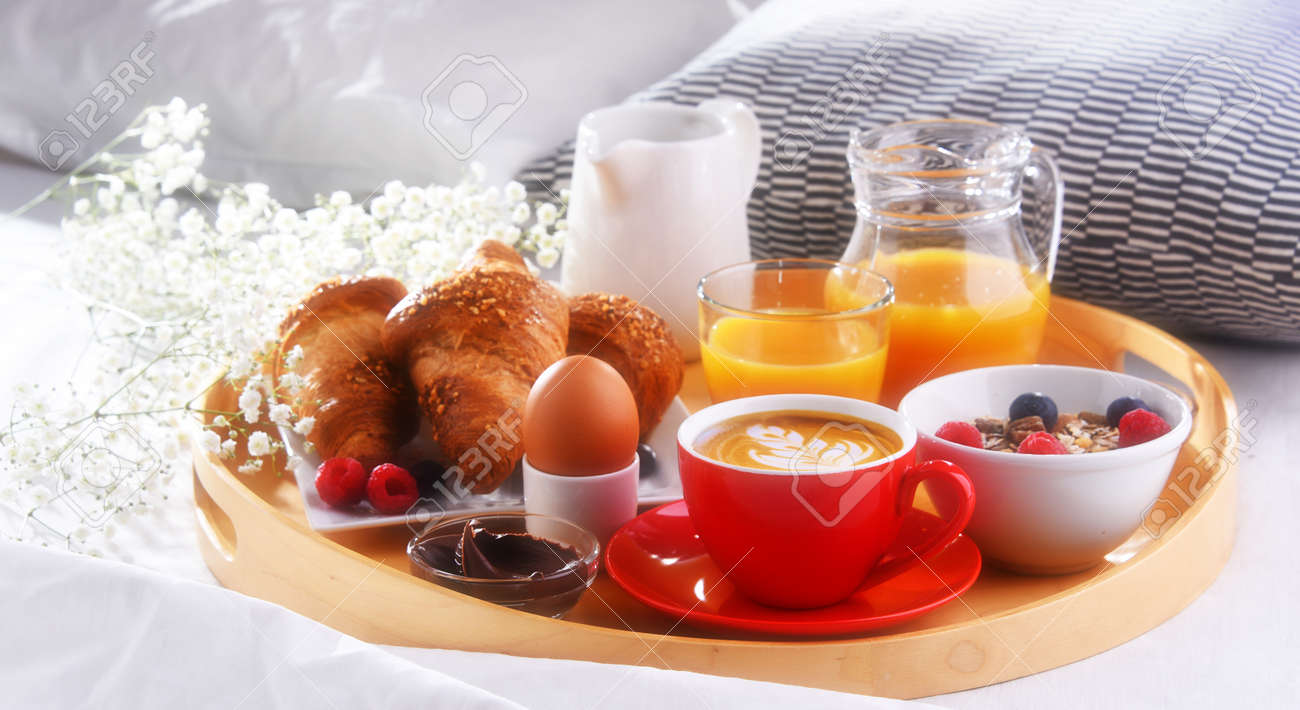 A tray with breakfast on a bed in a hotel room. - 168774957