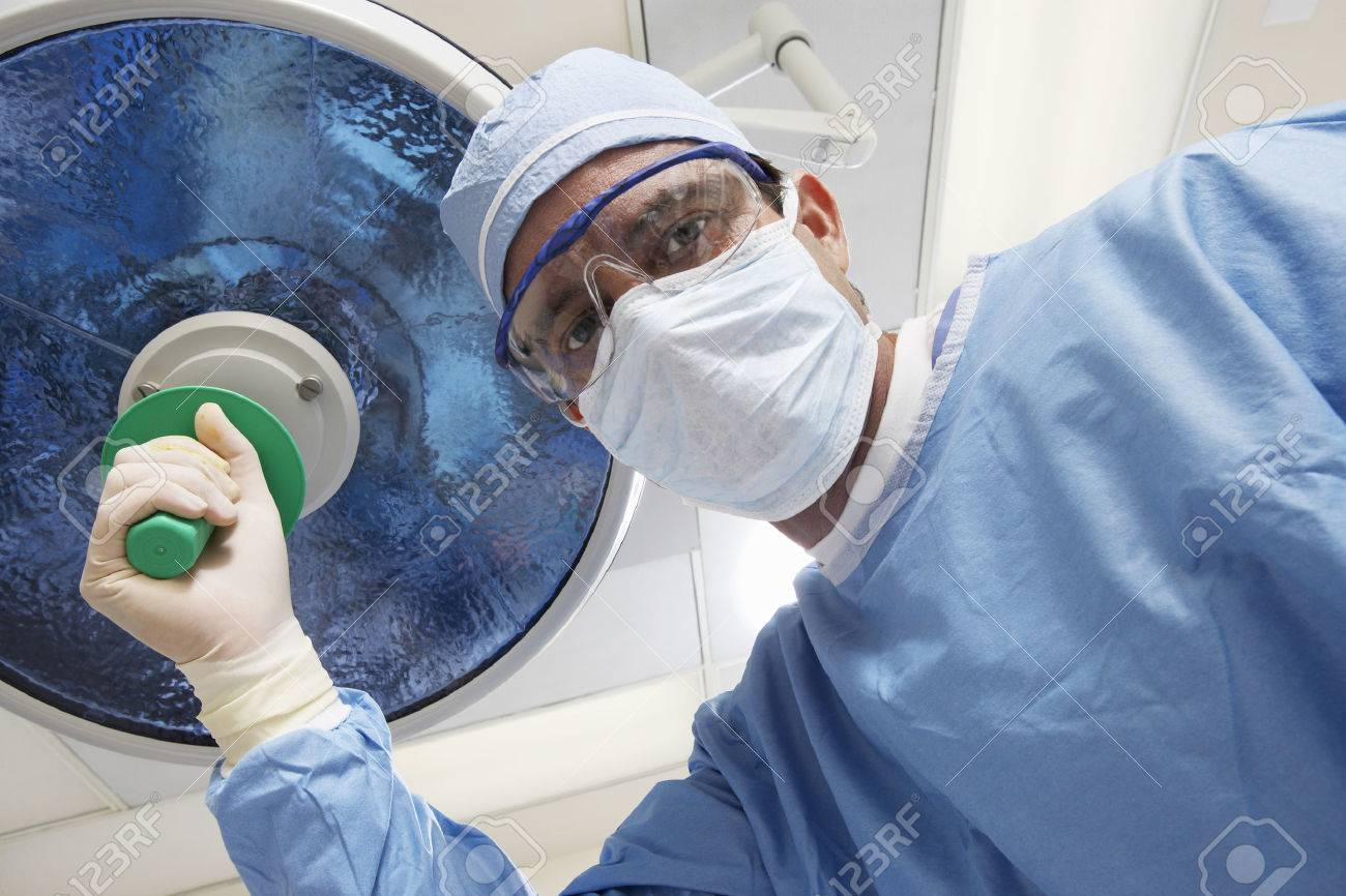 Surgeon adjusting lamp, low angle view Stock Photo - 3812359