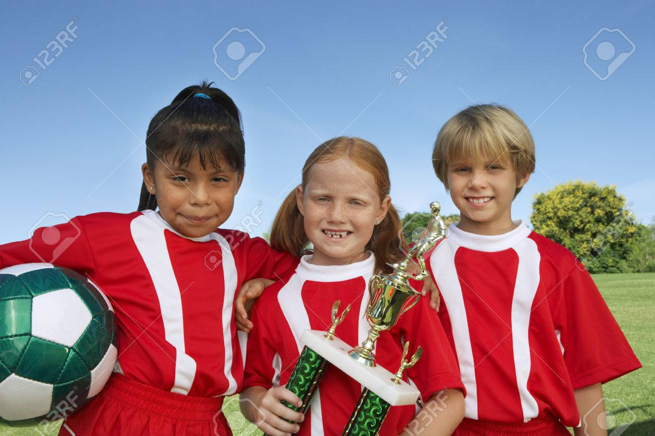 Three children (7-9 years) holding soccer ball and trophy on soccer field, portrait Stock Photo - 3812430