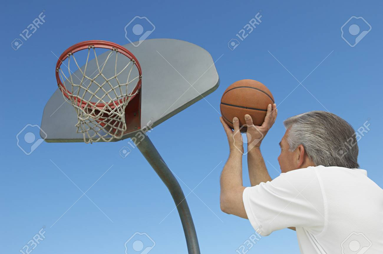 Senior man aiming basketball at hoop, outdoors Stock Photo - 3812510