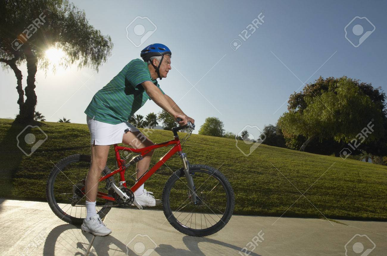 Senior man cycling in park at dusk, side view Stock Photo - 3812691