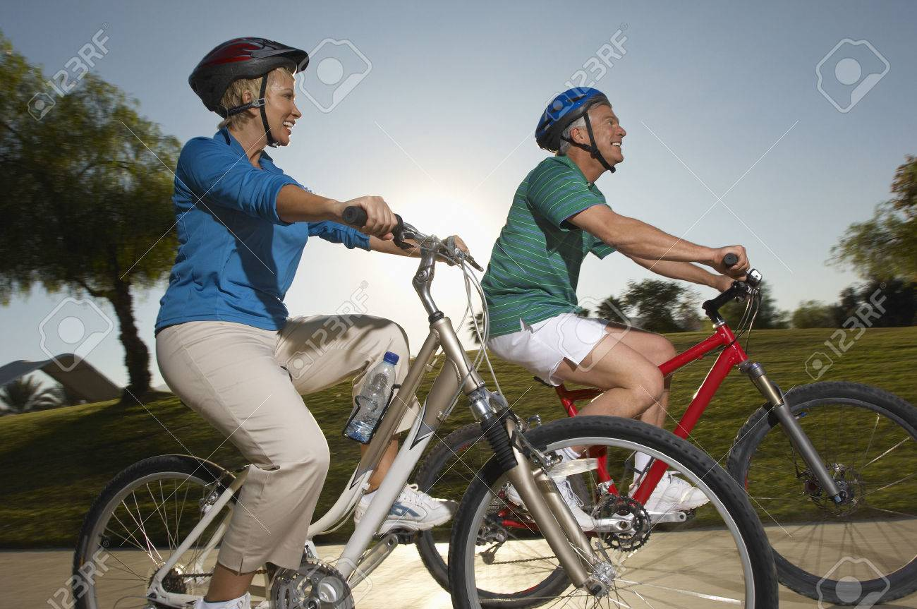 Senior couple cycling in park at dusk Stock Photo - 3812588
