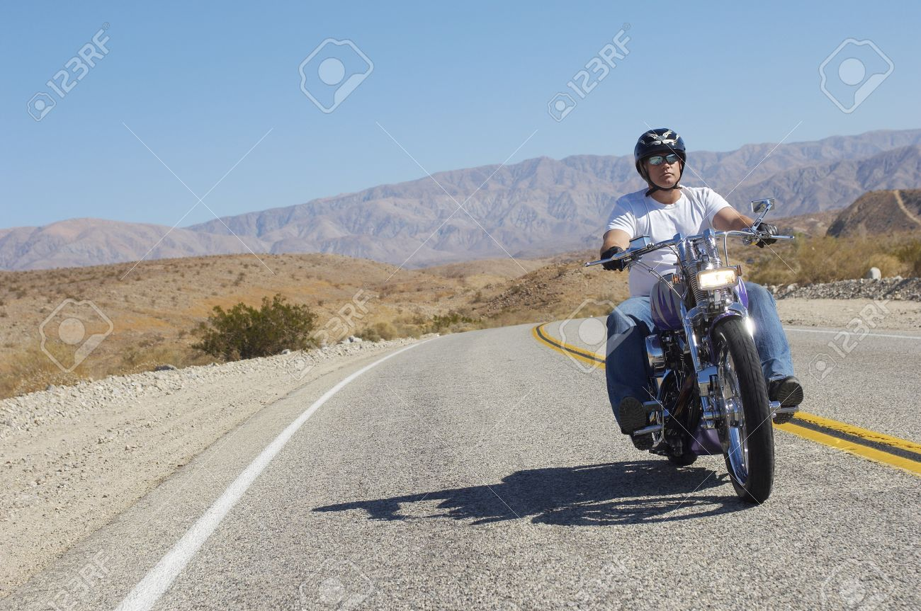 Man riding motorcycle on desert road Stock Photo - 3812686
