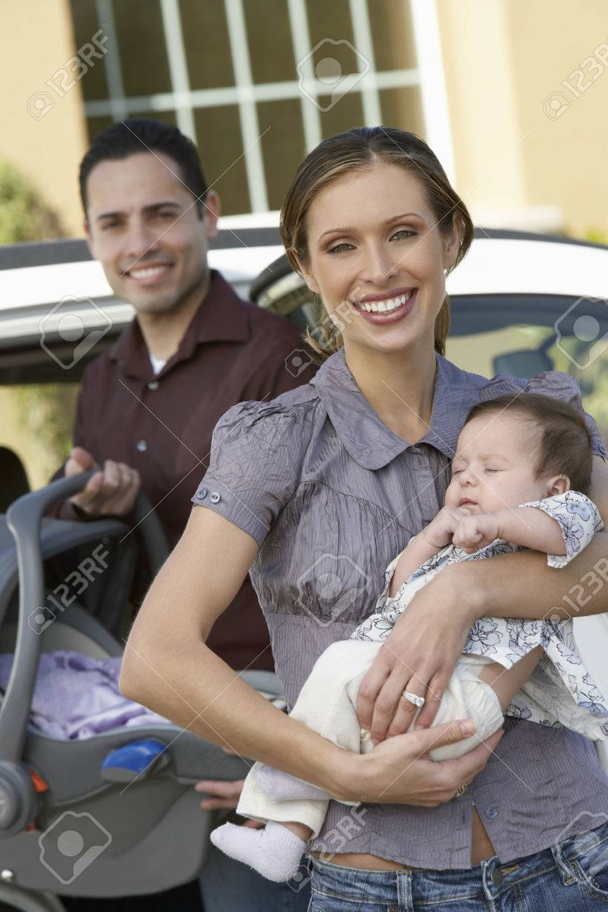Portrait of woman with baby (1-6 months) by car, man in background Stock Photo - 3812196