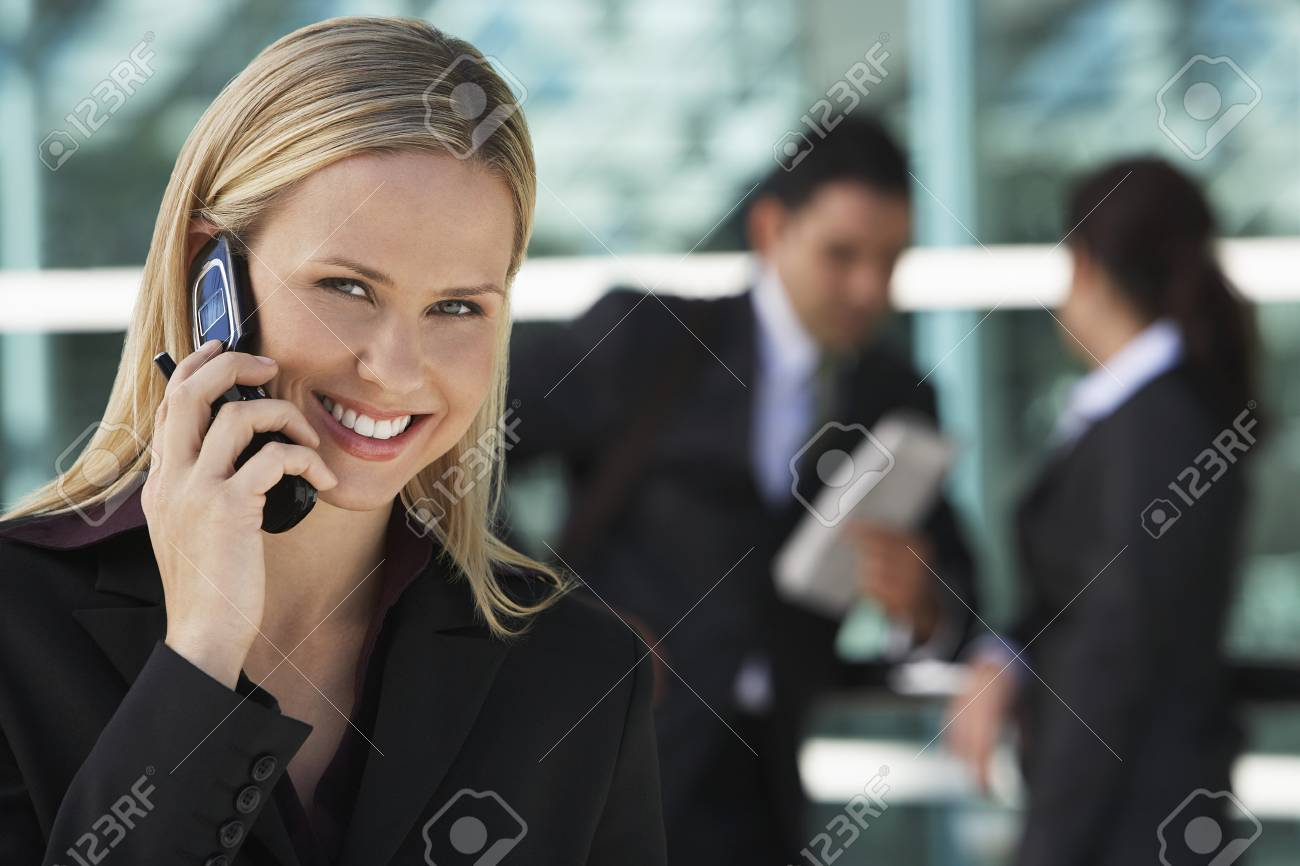 Businesswoman using mobile phone with colleagues in background, outdoors Stock Photo - 3811443