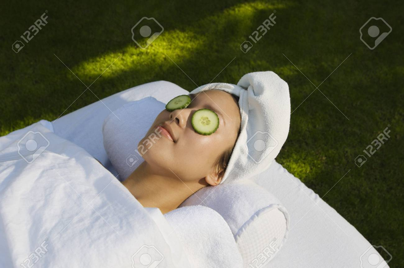 Young woman with cucumbers over eyes, lying on massage table outdoors Stock Photo - 3811451
