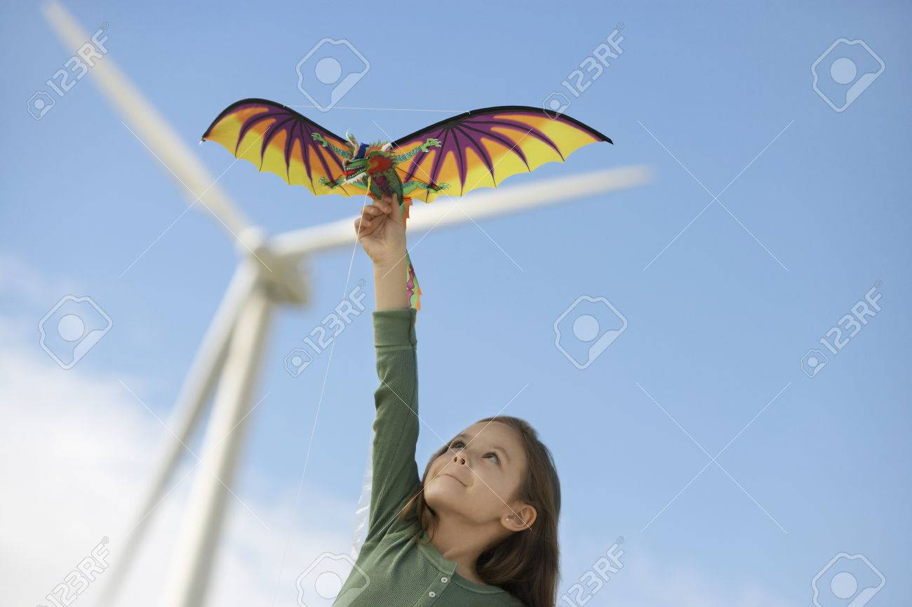 Girl (5-6) playing with kite at wind farm Stock Photo - 3811618