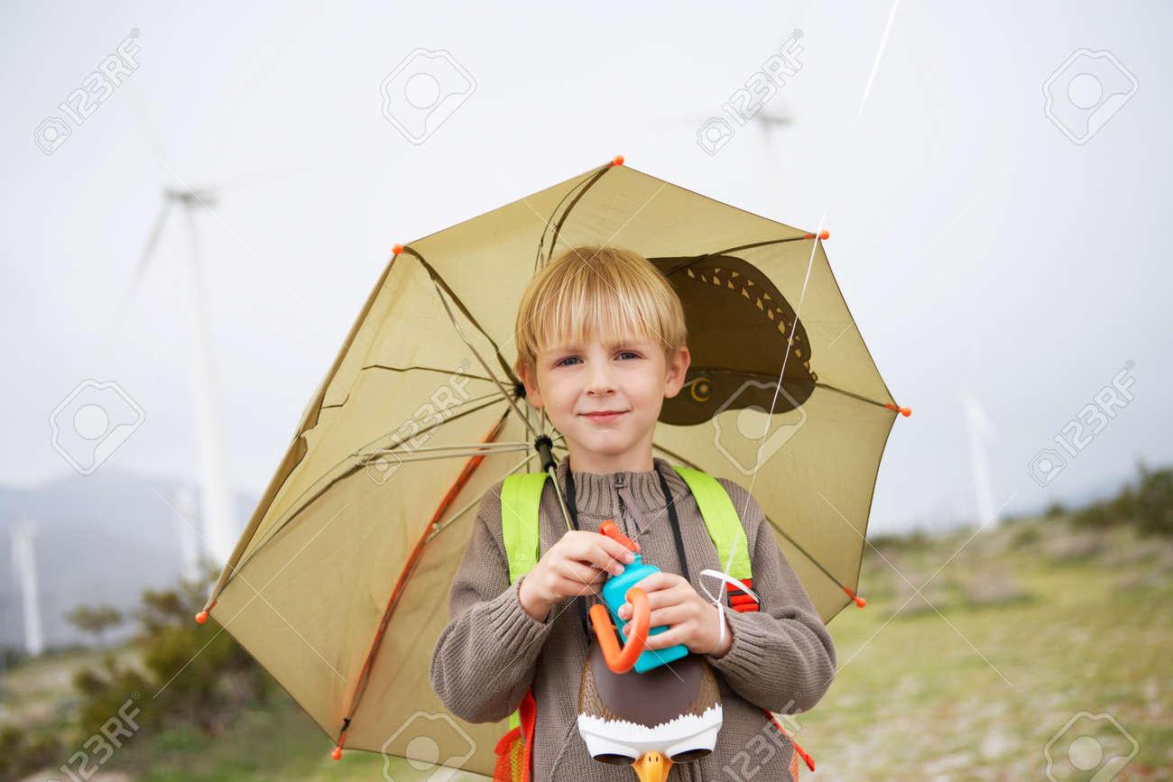 Boy (7-9) with umbrella at wind farm, portrait Stock Photo - 3811601
