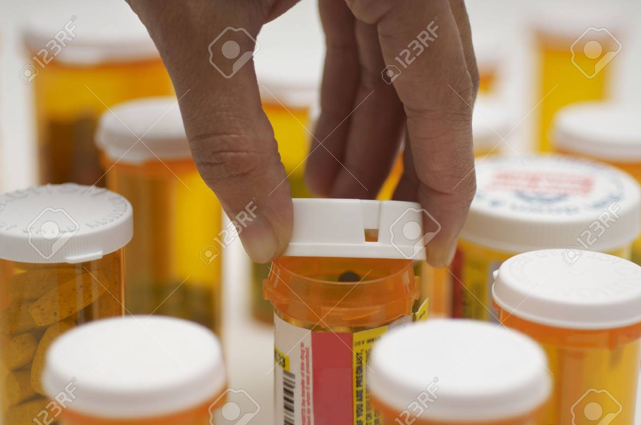 Man's hand opening pill bottle, close-up Stock Photo - 3811835