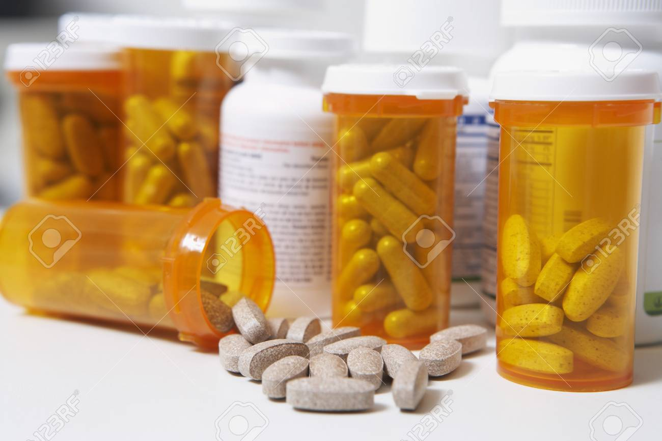 Bottles of pills, one spilling, close-up Stock Photo - 3812828
