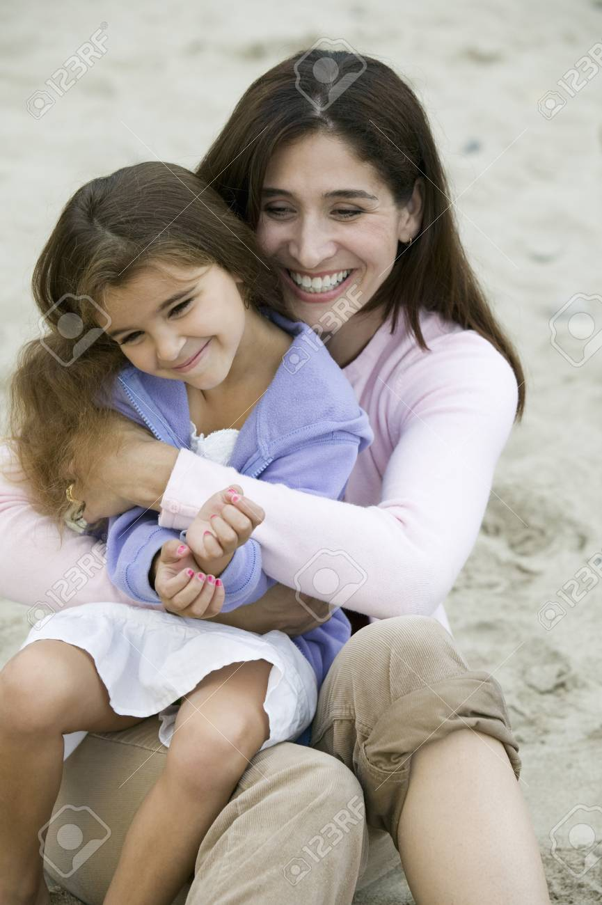 Mother embracing daughter on beach Stock Photo - 4926040