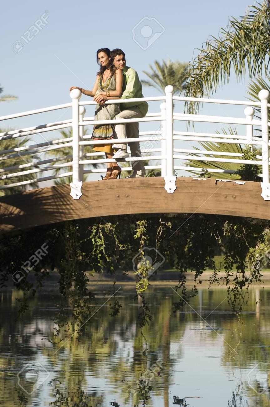 Couple embracing on bridge in park Stock Photo - 4926095