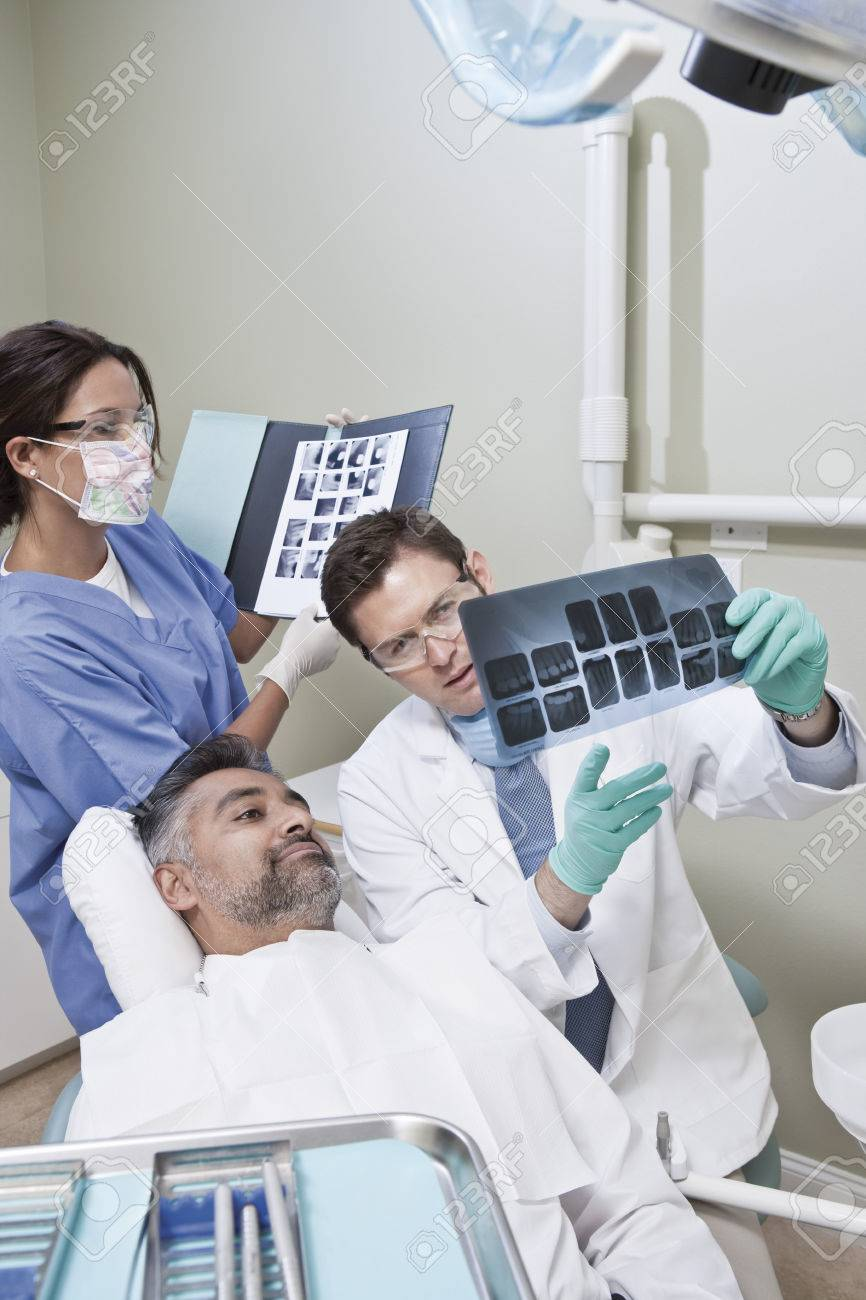 Dentist and patient looking at x-ray Stock Photo - 4925998