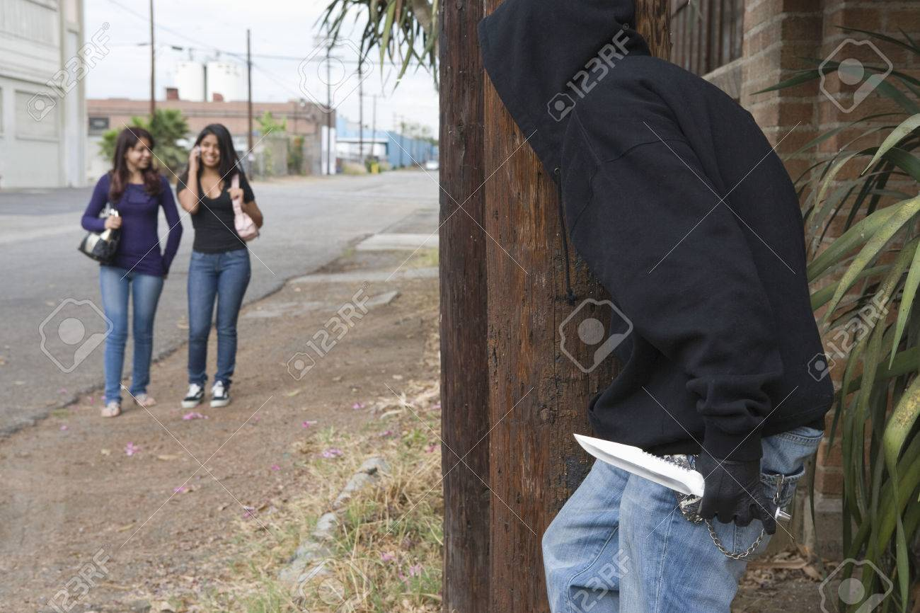 Robber with knife hiding behind tree and waiting for two girls Stock Photo - 4926156