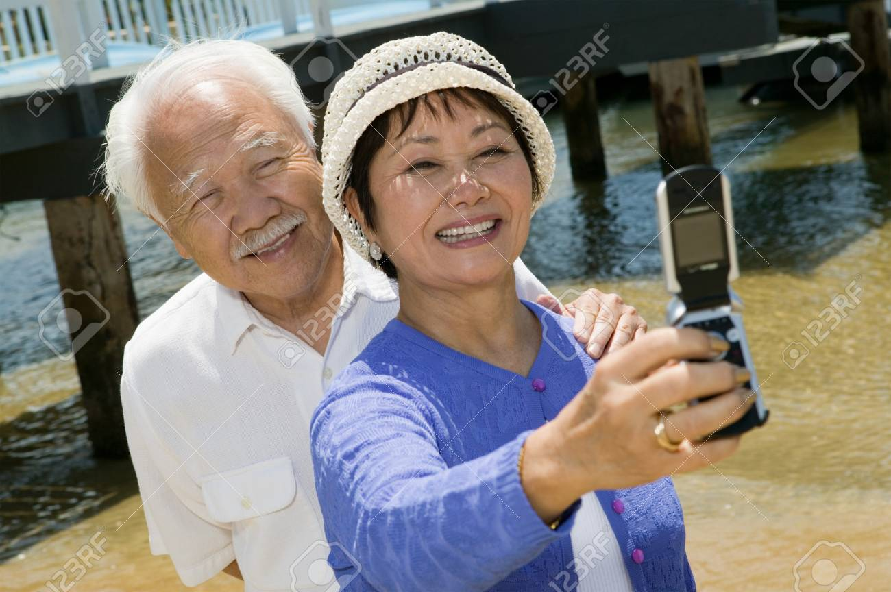 Couple Taking Their Own Photograph with Camera Phone Stock Photo - 5412309