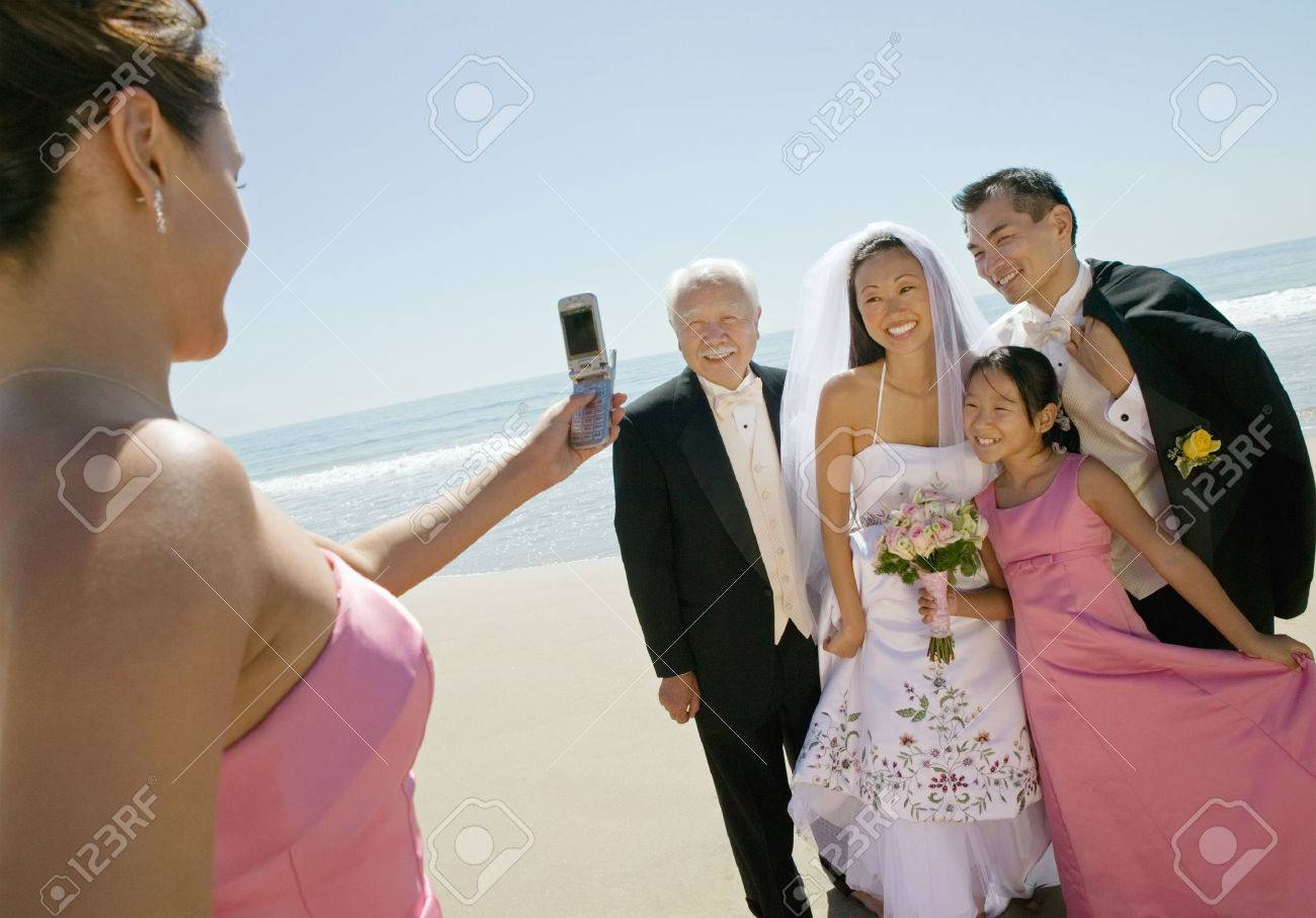Bridesmaid Taking Picture of Newlyweds and Family Stock Photo - 5412445