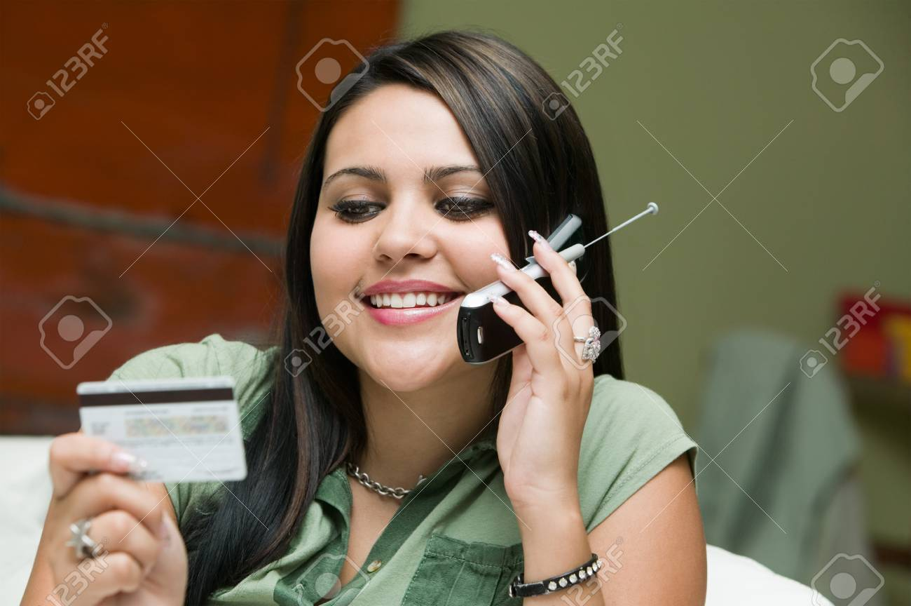 Woman Holding Credit Card Using Cell Phone Stock Photo - 5428280