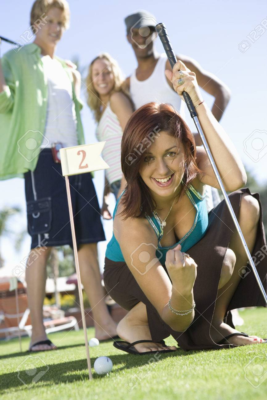 Young woman playing mini golf with friends Stock Photo - 5404314