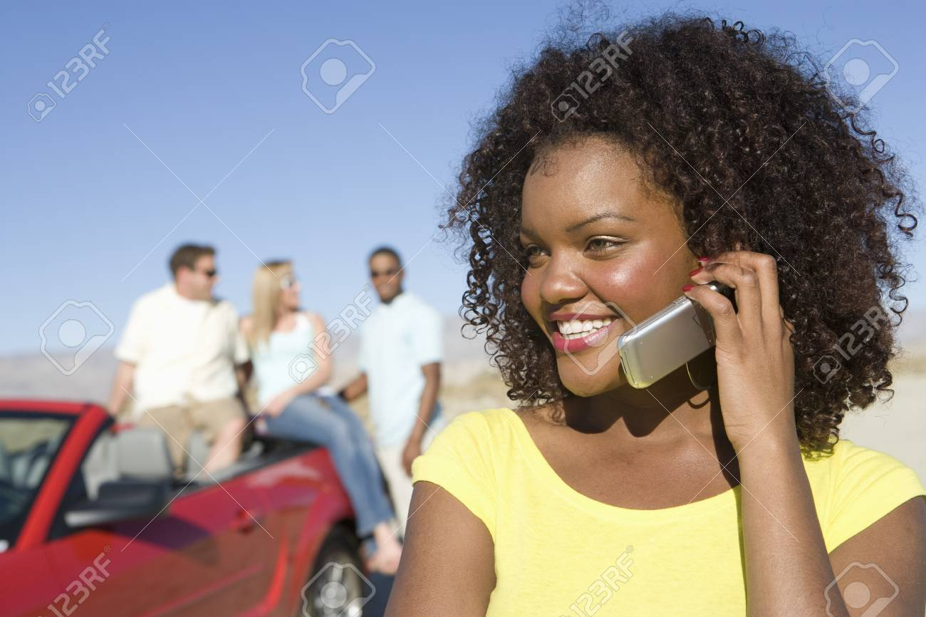 Portrait of young woman with mobile, others in background Stock Photo - 5459998