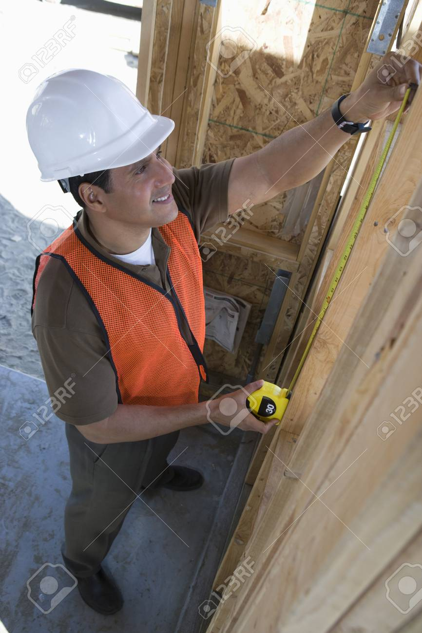 Construction worker measuring wall with measure taper inside half constructed house Stock Photo - 5470408